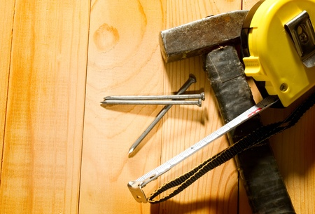 Hammer, tape measure and nails isolated on the wooden background photo