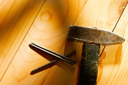 Hammer and nails isolated on the wooden background photo