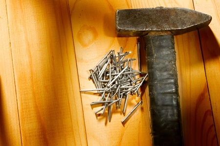 Hammer and nails isolated on the wooden background Stock Photo - 10831387