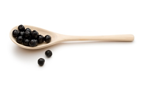 bacca: Black chokeberry in a spoon isolated on the white background