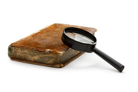 Magnifying glass and old book isolated on white  photo