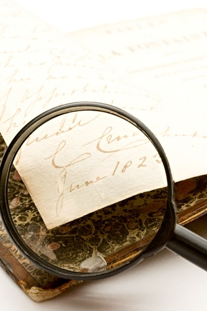 Magnifying glass and old book on the white background photo