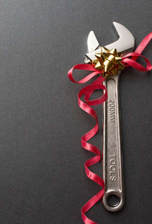 Spanner with ribbon on the grey background photo