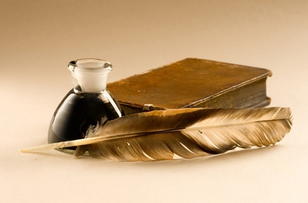 An old book with a feather and the inkpot full of ink  photo