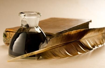 Ein altes Buch mit einer Feder und das Tintenfass voller Tinte