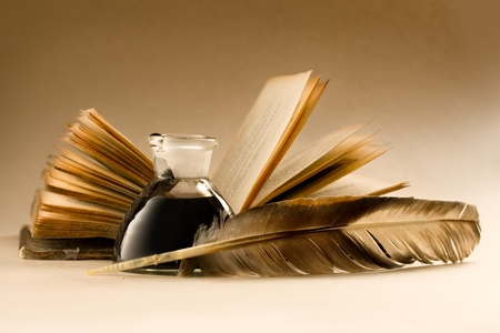 An old book with a feather and the inkpot full of ink  Stock Photo