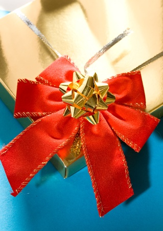 Golden gift box decorated with red and silver ribbons photo