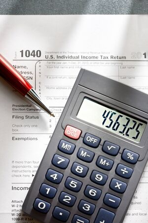 tax forms: Tax form, red pen and calculator Stock Photo