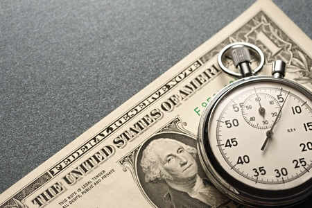 Stopwatch and dollars on a grey background photo