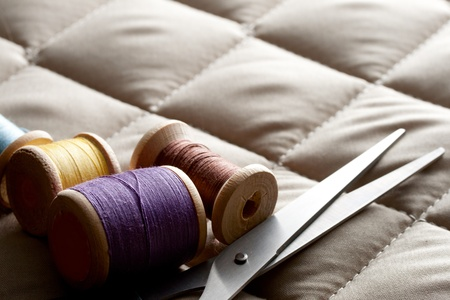 Thread bobbins with scissors on a gray fabric photo