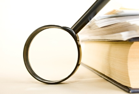 magnifying glass: A pile of paper and a book through the magnifying glass