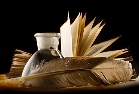 quill pen: A feather with the bottle full of ink and a book Stock Photo