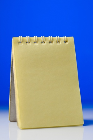 A yellow notepad on a blue-and-white background photo