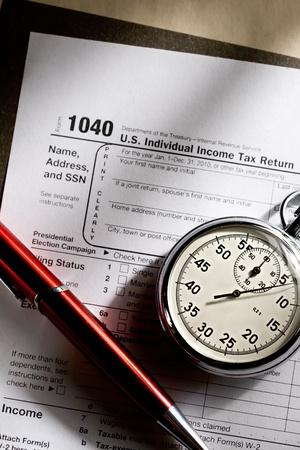 retour: Belastingformulier, rode pen en stopwatch Stockfoto