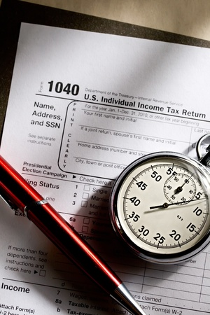 tax return: Tax form, red pen and stopwatch
