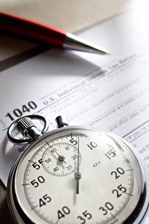 retour: Belastingformulier, stopwatch en pen Stockfoto