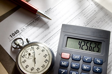 Tax form, stopwatch, calculator and pen photo