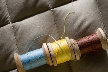 Thread bobbins on a gray fabric photo
