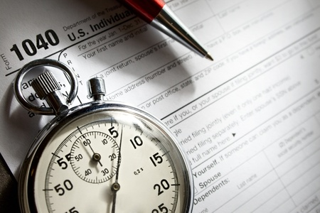 Tax form, red pen and stopwatch photo
