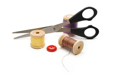 Thread bobbin, scissors and buttons on the white background  photo