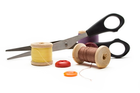 Thread bobbin, scissors and buttons on the white background