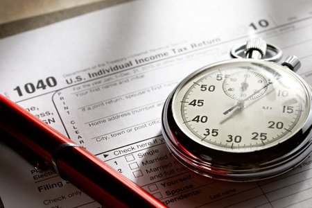 tax forms: Tax form, red pen and stopwatch