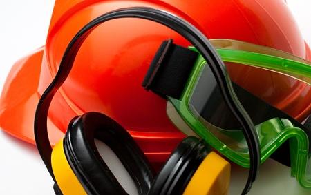 elementos de protecci�n personal: Casco de seguridad rojo con gafas y aud�fonos Foto de archivo