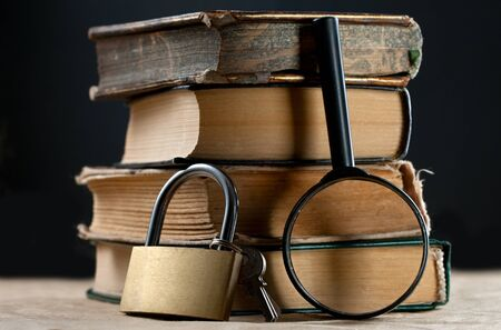keylock: Pile of old books with keylock and magnifying glass