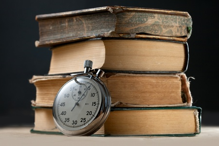 end of time: Pile of old books and stopwatch