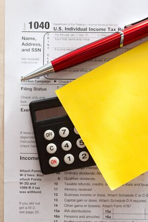 Tax form, red pen, calculator and sticker