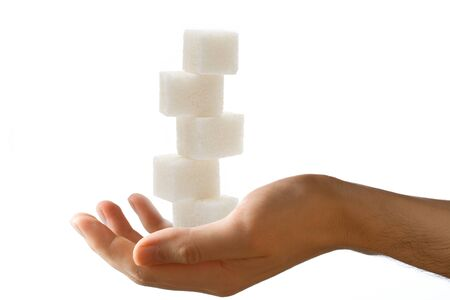sweetening: Male hand with sugar cubes