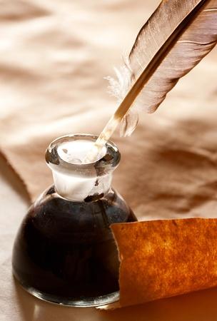 pluma de escribir antigua: Pluma y tintero sobre fondo de papel