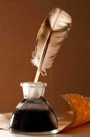 Feather and ink bottle on paper background Stock Photo - 12953055