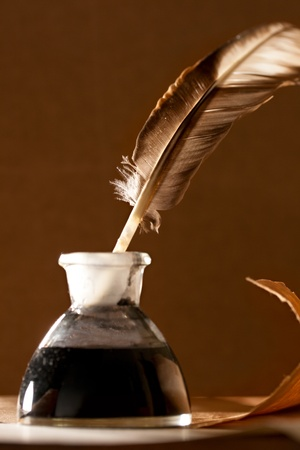 Feather and ink bottle on paper background  photo
