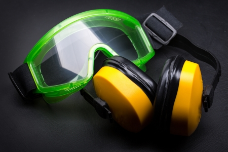 protecting spectacles: Green goggles with earphones on black Stock Photo