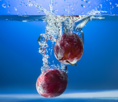 fruit drop: Fresh plums in water splash
