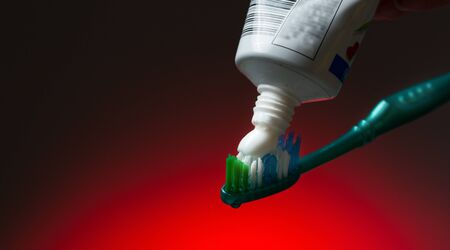 Toothbrush and toothpaste on red photo