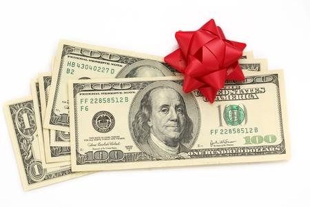christmas profits: Dollars with decorative bow on white
