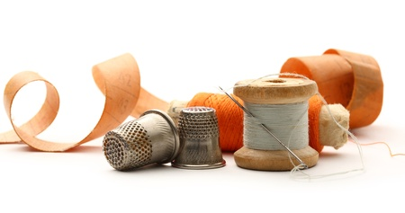Sewing thimbles, bobbins and needle photo