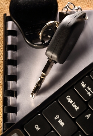 Notebook, car key and computer keyboard  photo