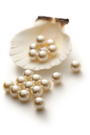 Scattering white pearls in seashell 스톡 콘텐츠