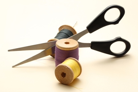 Thread bobbin and scissors on the white background  photo