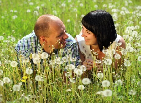 Young couple lying on grass in the field of dandelion photo