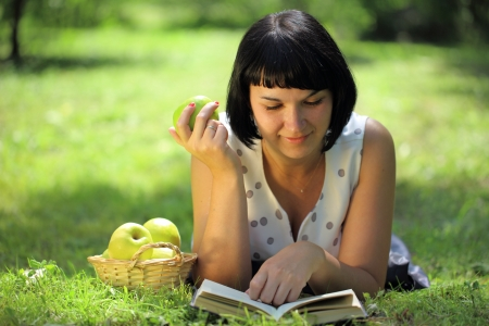 Young woman holding apple and reading book on grass photo
