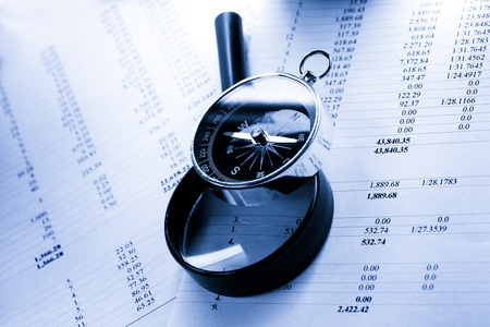 Operating budget, magnifying glass and black compass photo