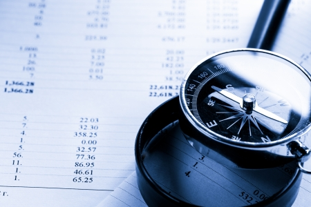 financial paperwork: Operating budget, magnifying glass and black compass