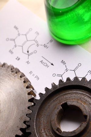 Chemistry formula with green flask and mechanical cogwheels photo