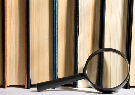 Stack of books and magnifying glass photo