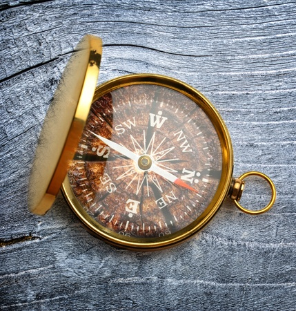 Compass on gray wooden background photo