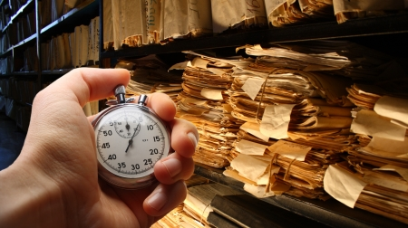Hand with stopwatch, paper documents stacked in archive photo